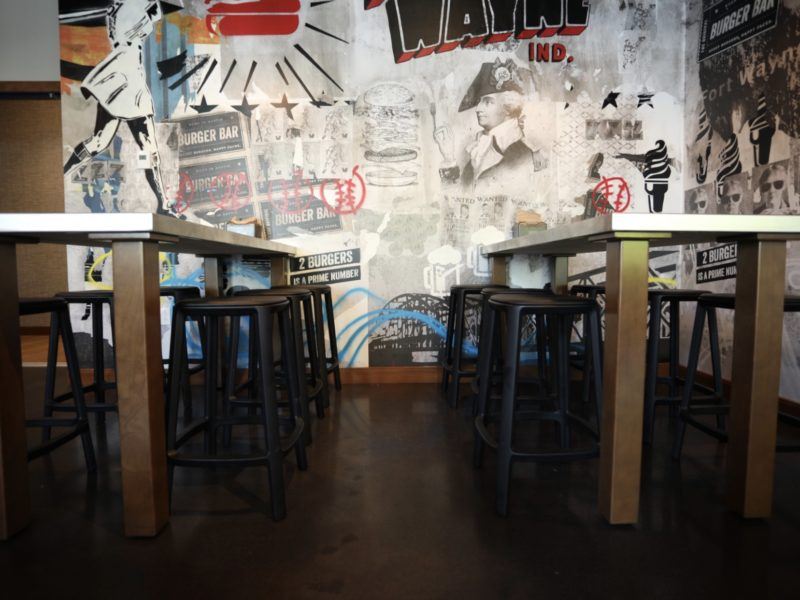 Tucked in stools under industrial tables in front of a busy wall