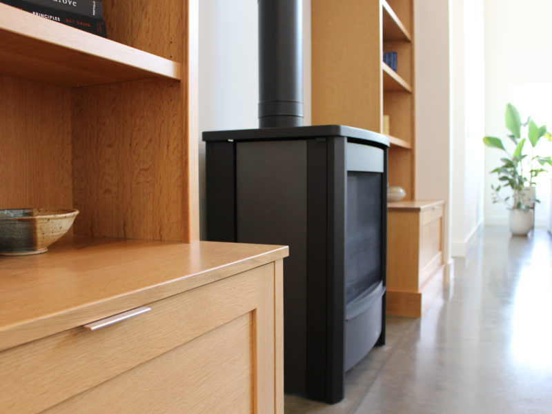 Close up of natural wood builtin cabinets with a black iron, wood burning stove on a polished concrete floor