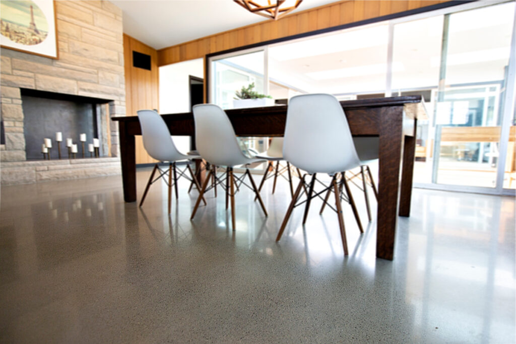 Polished Concrete floor in a dining room with white chairs, a wood table, and a fireplace.