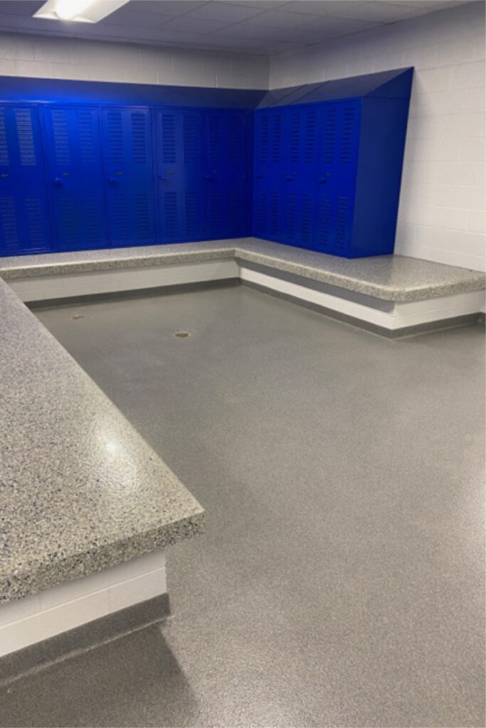 Locker room with blue lockers that have a slanted top; integral benches that have a decorative epoxy chip