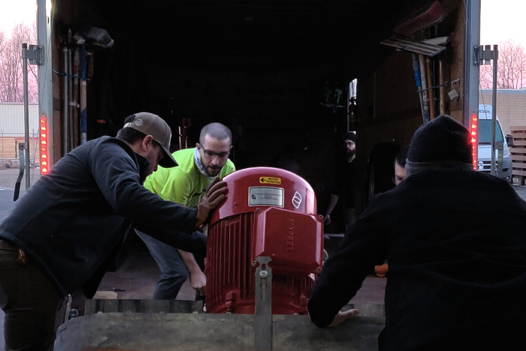 Four men are pushing a large machine onto a horse trailer.